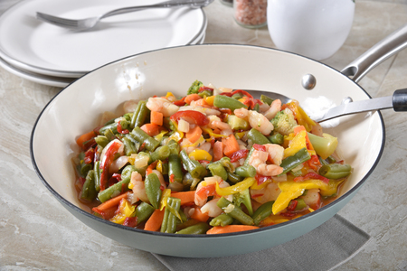 Gourmet shrimp stir fry with green beans and bell peppers in a cast iron skillet