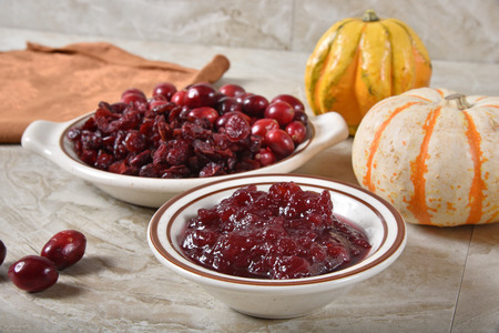 A bowl of cranberry sauce with dried and fresh cranberries in the background Stockfoto - 115757772