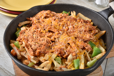 Close up of loaded french fries with pulled chicken, green bell peppers and cheeses