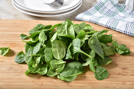 Fresh washed organic spinach leaves drying on a cutting board 免版税图像