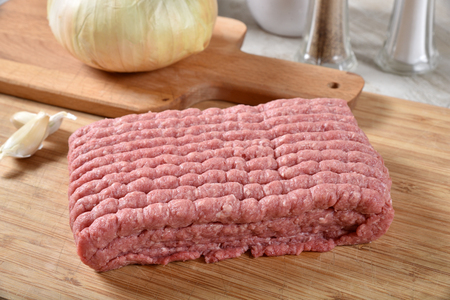 A pound of uncooked ground beef with garlic and onion Standard-Bild - 116885711