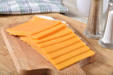 Thick slices of cheddar cheese on a wooden cutting board Stok Fotoğraf