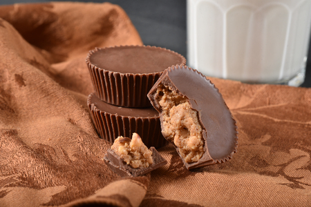 Gourmet chocolate covered peanut butter cups with a glass of milk