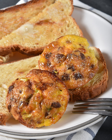 Closeup of baked sausage and cheese mini-omelets with buttered toast Фото со стока