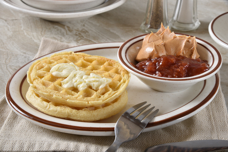 Hot buttered waffles with peanut butter and strawberry jam