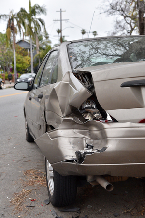 A wrecked car to the side of a street after an accident