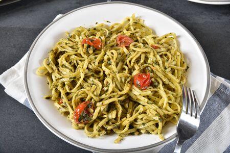 Ovherhead view of basil pesto linguine with tomatoes