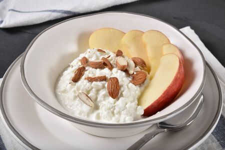Closeup of a bowl of cottage cheese with apple slices and almonds