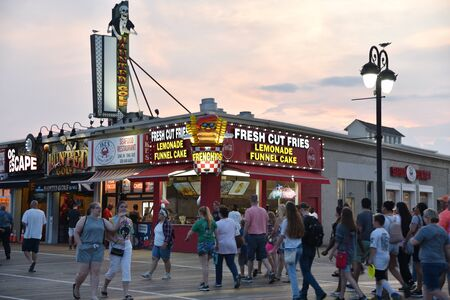 OCEAN CITY, NEW JERSEY/USA - JUNE 27, 2019: Tourists passing food stands and amusement arcades on the Ocean City Boardwalk at sunset