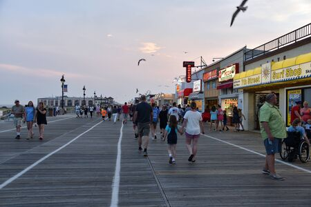 OCEAN CITY, NEW JERSEY/USA - JUNE 27, 2019: Tourists on the famous boardwalk in Ocean City New Jersey at dusk