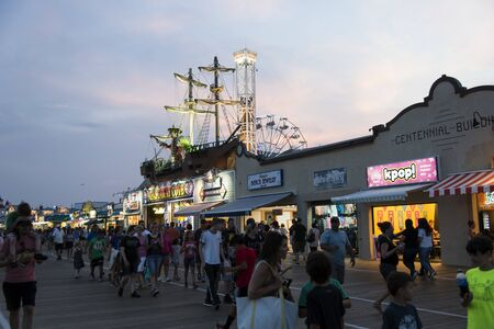 OCEAN CITY, NEW JERSEY/USA - JUNE 27, 2019: Tourists on the Ocean City Boardwalk during a vibrant sunset