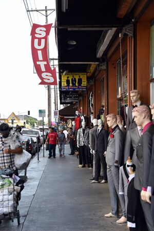 LOS ANGELES, CA/USA - JUNE 19, 2017: Shoppers, vendors and clothing mannequins line the sidewalk in the Los Angeles Fashion District.