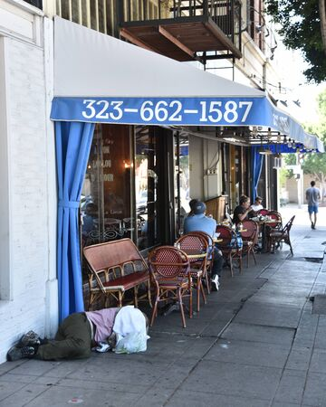 LOS ANGELES, CA/USA - JULY 10, 2019: Homeess man sleeps on the sidewalk near sidewalk tables of an exclusive French restaurant on Vermont Street