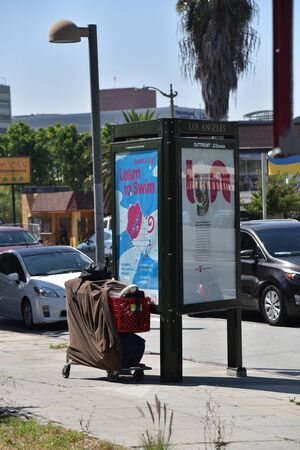 LOS ANGELES, CA/USA - JULY 10, 2019: Homeless person's posessions in a shopping cart by a bus stop shelter on a busy street