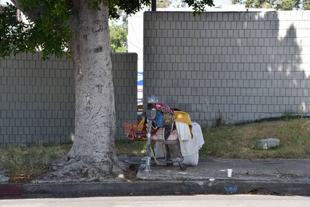 LOS ANGELES, CA/USA - JULY 10, 2019: A homeless person's possessions in a shopping cart by a parking meter