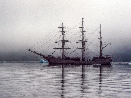 An old-fashioned Schooner style-ship sits anchored in Port Lockroy, Antarctica Stock Photo