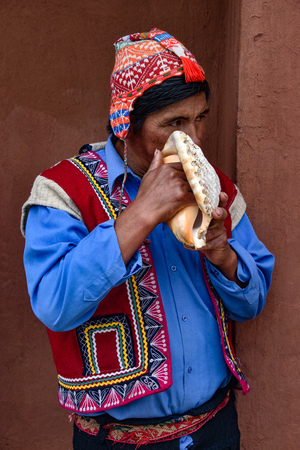 Sacred Valley, Cusco, Peru - Oct 13, 2018: An indigenous Quechua man blows on a Conch Shell Editorial