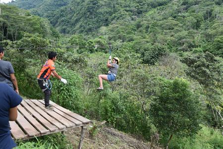 Junin, Peru - Dec 31, 2018: Adventurous tourists ziplining over a river in the Chanchamayo region