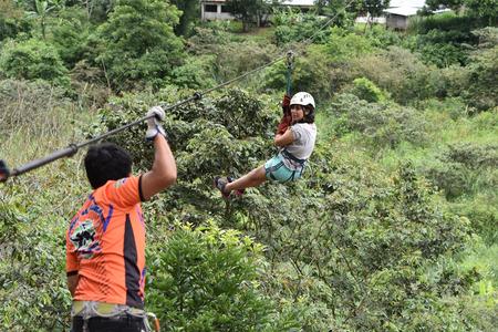 Junin, Peru - Dec 31, 2018: Adventurous tourists ziplining over a river in the Chanchamayo region Archivio Fotografico - 126534756