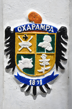 Oxapampa, Peru - Dec 31, 2018: The Oxapampa coat of arms painted on a lamp post in the Plaza de Armas