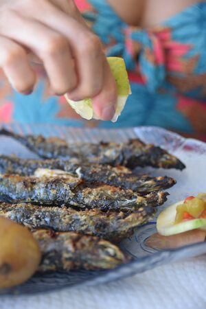 Lison, Portugal: A diner squeezes lemon juice onto freshly grilled Sardines 版權商用圖片
