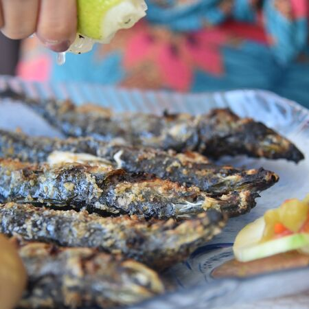 Lison, Portugal: A diner squeezes lemon juice onto freshly grilled Sardines 스톡 콘텐츠