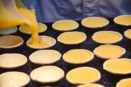 Pasteis de Nata, traditional Portuguese pastries, being made in a Lisbon bakery