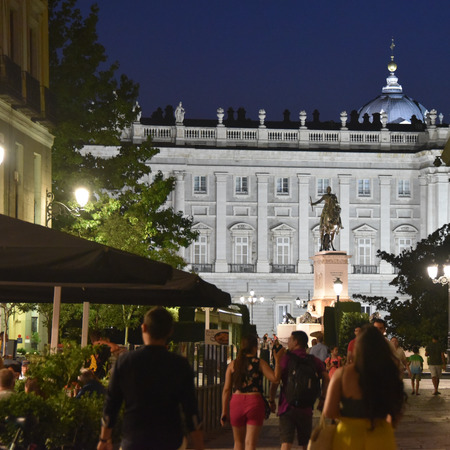 Madrid, Spain - July 20, 2019: Pedestrians take an evening stroll near the Palacio Real de Madrid Redactioneel