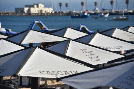 Cascais, Portugal - July 24, 2019: Parasols and sun loungers on the beach in the resort town of Cascais, Portugal