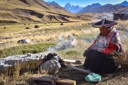 A Quechua lady uses natural dyeing techiques to color Alpaca Wool for textile making. Chillca, Cusco, Peru