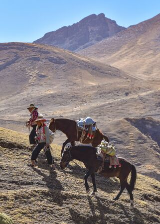 Horsemen in traditional Quechua dress following trails through the Andes. Ausungate trail, Cusco, Peru Stock Photo