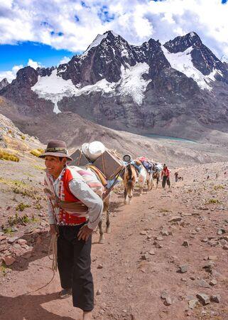 Horsemen in traditional Quechua dress following trails through the Andes. Ausungate trail, Cusco, Peru 스톡 콘텐츠