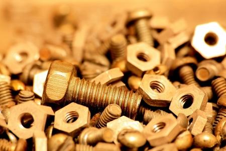 pezones: Una gran cantidad de pernos metálicos y los pezones están en la mesa de trabajo Foto de archivo