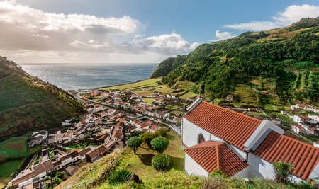 Small village Faial da Terra between rolling hills in warm afternoon light on Sao Miguel Island in the Azores Standard-Bild