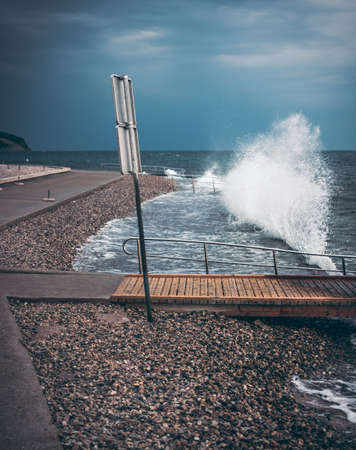 Breaking waves on promenade with warning sign