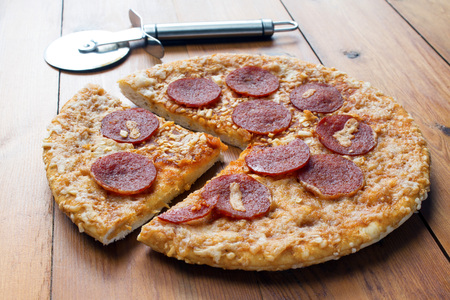 pizza cutter: Pepperoni and cheese pizza on a wooden board with a pizza cutter Stock Photo