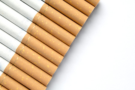 ciggy: Cigarettes in a row on an isolated white background with copyspace for additional messages