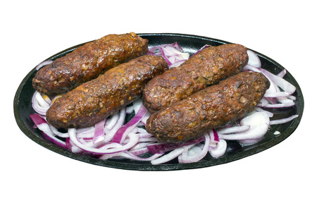 sizzling: Kofta kebabs and red onions on a sizzling hot plate against an isolated white background with a clipping path
