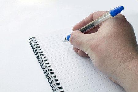 ball point: Male hand close up writing with a ball point pen on a notepad on a white background