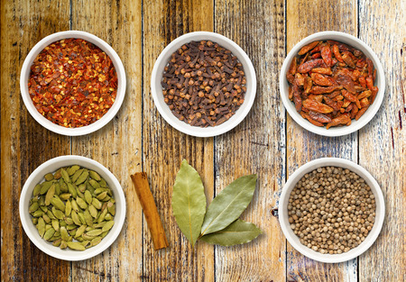 cinnamon stick: Spices including chilli flakes, cloves, birds eye chillies, cardamoms, cinnamon stick, bay leaves and coriander seeds in white pots on a distressed wooden board Stock Photo
