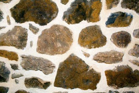 plastered wall: Stone wall texture with brown uneven sized rocks with large plastered areas