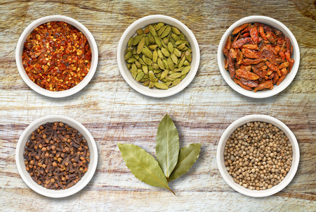 scored: Spices including chilli flakes, cloves, birds eye chillies, cardamoms, bay leaves and coriander seeds in white pots on an old scored wooden kitchen cutting board Stock Photo