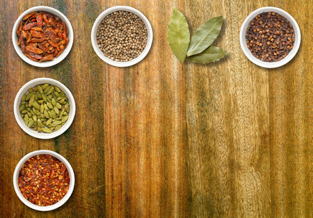 coriander seeds: Spices including chilli flakes, cloves, birds eye chillies, cardamoms, bay leaves and coriander seeds in white pots on an old dark wood chopping board with copy space Stock Photo