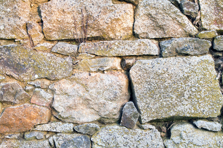 gaps: Stone wall texture made from uneven sized rocks with twigs and cobwebs in the gaps Stock Photo