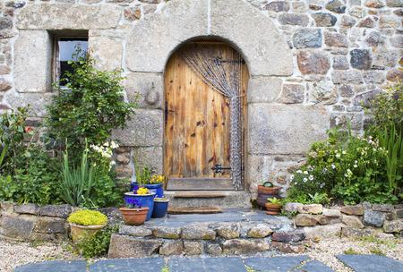 Porte et fenêtre rustiques en bois français décorées de plantes en Bretagne France