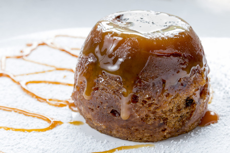 Sticky toffee pudding close up on a white sugar dusted plate drizzled with caramel sauce Stock Photo
