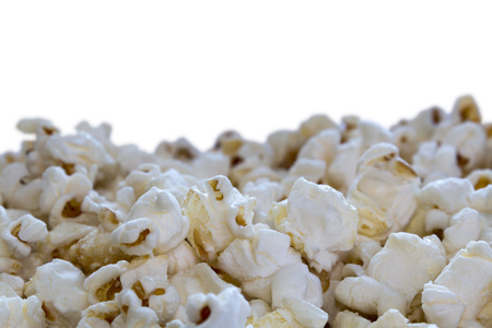 Popcorn in a pile close up with a shallow depth of field on an isolated white background with copy space