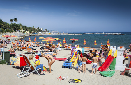 Sanremo, Liguria, Italy - May 23, 2009: People relaxing on a Mediterranean public beach in Sanremo Italy on a hot summer day