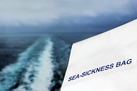 Sea sickness bag against a stormy ocean background with wake from a ship and a shallow depth of field Stockfoto