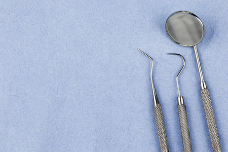Dentist tools including a mirror, sickle scrapper and tooth probe on a hygienic blue disposable cloth from an overhead perspective with copy space